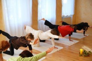 Pilates, foto van dames die op 1 knie zitten op een matje met een arm naar voren