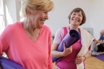 Foto van 2 lachende dames met een yogamat onder de arm