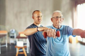 Foto van een trainer en een man die gewichtjes omhoog houdt