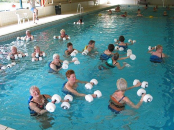 Aquagym, foto van een groep dames met gewichten in de hand krijgt les in het zwembad