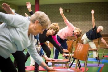 Beweeg U Fit, foto van een groep vrouwen die een oefening met een stoel doet in de gymzaal