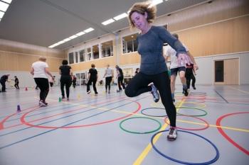 sportende mensen in de gymzaal doen een parcours met ringen