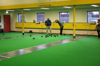 Bowls, foto van 2 mannen die in een zaal bowls spelen