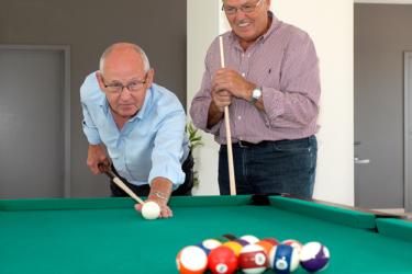 Biljart, foto van 2 mannen die een pot poolbiljart spelen