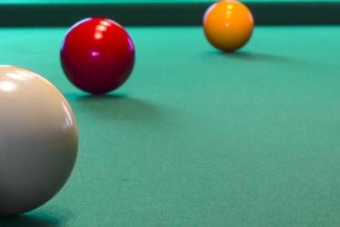 Biljarten, foto van 3 ballen op een biljart met een keu