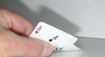 Bridge,foto van een hand met 2 speelkaarten, 2 azen.