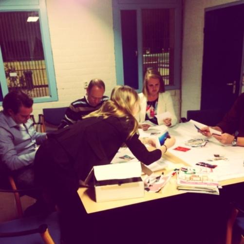 Foto van een groep mensen om een tafel die zitten te brainstormen