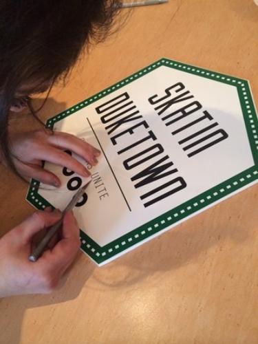 Foto van een vrouw die het logo van Skatin Duketown aan het bewerken is