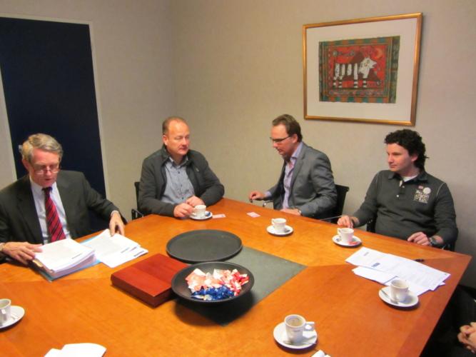 Foto van een groep mensen, zittend om een tafel waarbij een akte wordt ondertekend