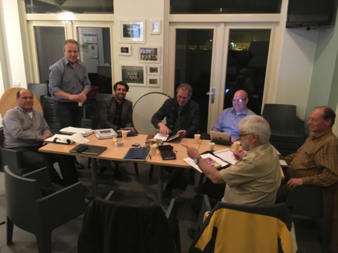 Foto van een groep mensen in vergadering om een tafel