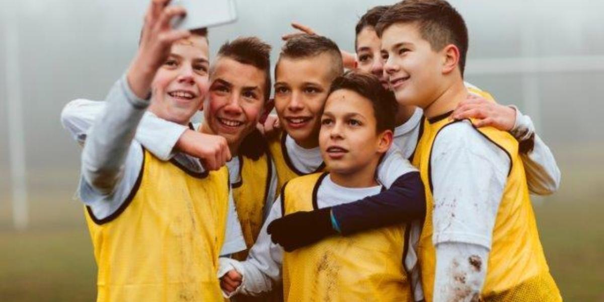 Foto van een klein Voetbal Team Jongens Maakt Selfie