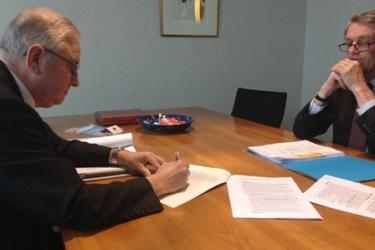 Foto van Henk van den Wassenberg die tekent namens Nimrod bij de Notaris
