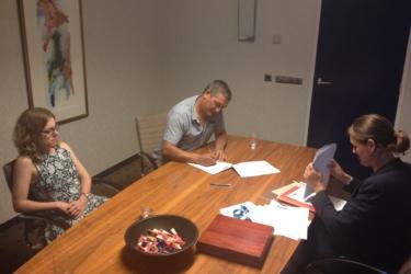 Foto van 3 mensen om een tafel waarbij 1 iemand papieren ondertekend