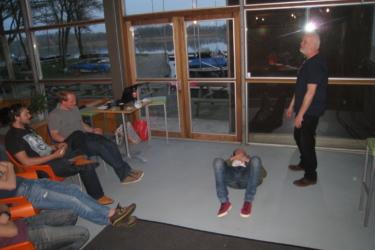 foto van een groep mensen zittend op een stoel, kijken naar iemand die op de grond ligt