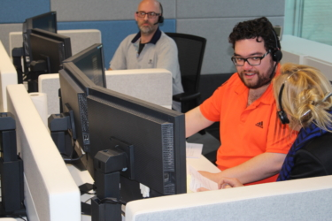 Foto van 3 mensen die aan tafels zitten met schermen er tussen en een headset op