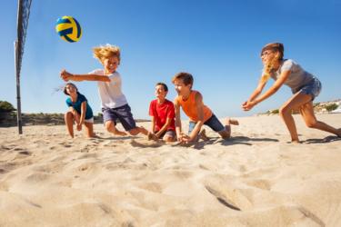Kinderen sporten buiten zon beachvolleybal